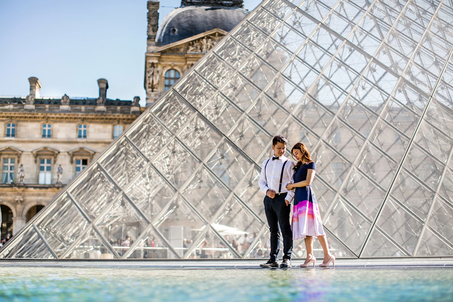 Prewedding photoshoot Paris in front of the Louvre Museum glass pyramid